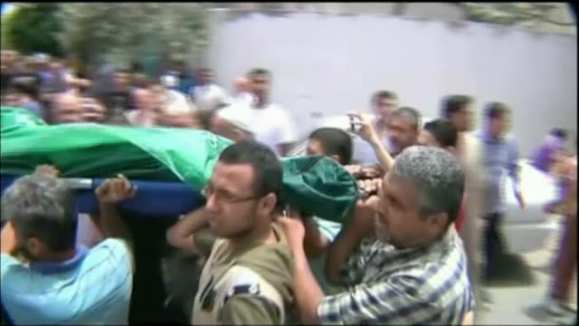 gaza conflict continues as calls for ceasefire mount; bodies wrapped in green cloth tilt up mourners men carrying body along on stretcher high angle... - ceasefire stock videos & royalty-free footage
