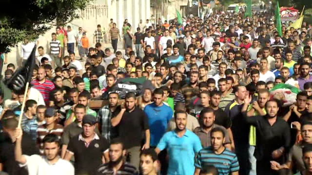 calls for ceasefire as israeli bombardment hits home for disabled; israel: gaza: ext crowds along street for funerals of victims of bombardment body... - ceasefire stock videos & royalty-free footage
