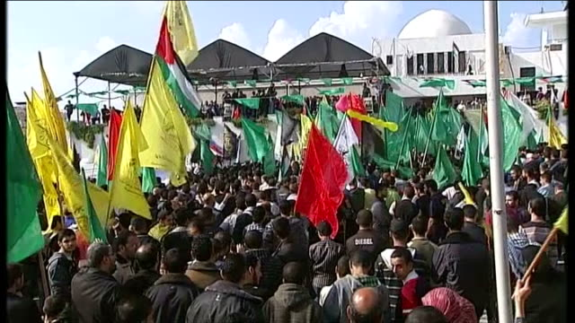 israelipalestinian conflict first day of ceasefire israel gaza ext palestinians waving yellow green and red flags celebrating first day of ceasefire... - jihad stock videos & royalty-free footage