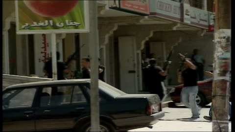 continued fighting between hamas and fatah groups; ext fatah gunmen firing weapons into the air and running through street where hamas offices are... - ガザ地区点の映像素材/bロール