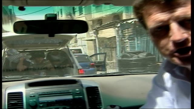 continued fighting between Hamas and Fatah groups Fatah gunmen in car ahead PULL OUT Reporter to camera