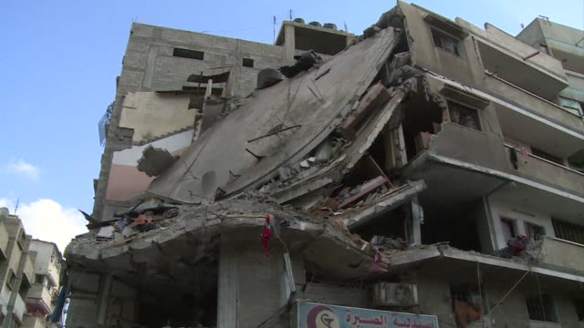 gazans pick through the rubble of a four storey building that was destroyed in an israeli bombardement on friday looking for their possessions - building storey stock videos and b-roll footage