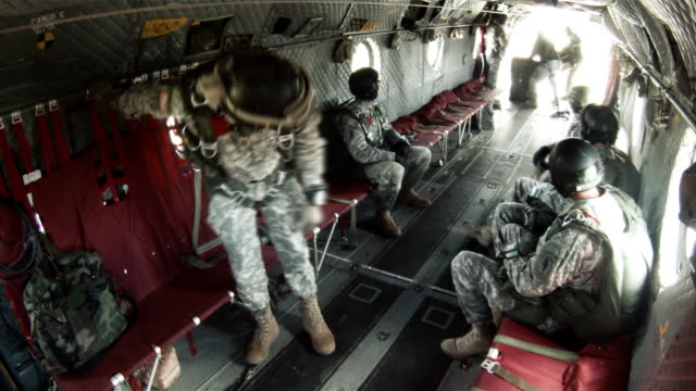 Gear being thrown out the back of a Chinook helicopter.