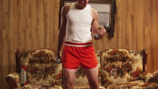ms tu geek man lifting dumbbells in living room / orem, utah, usa - ebete video stock e b–roll