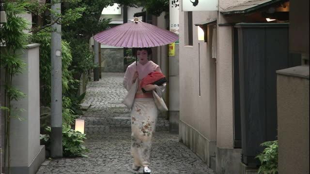 vídeos de stock e filmes b-roll de geisha holding parasol walks along cobbled alleyway - bairro antigo