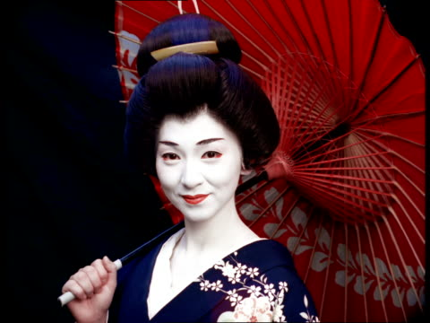 a geisha in traditional dress and white makeup holds a parasol and smiles. - kimono stock videos and b-roll footage