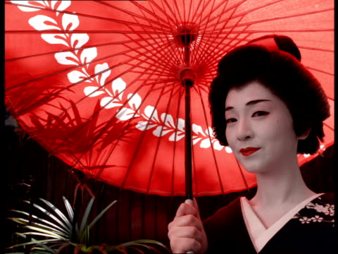 vidéos et rushes de a geisha in traditional dress and white makeup stands under a parasol and smiles. - geisha