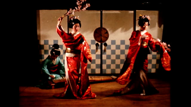 vidéos et rushes de / geisha sits on floor playing instrument / two geisha girls appear on the small stage and begin to dance / dinner patrons applaud. geishas perform... - geisha