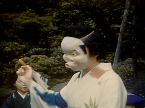 vidéos et rushes de 1953 mg geisha troupe. woman in kimono performing comic dance with two masks, one representing man, other woman / japan - geisha