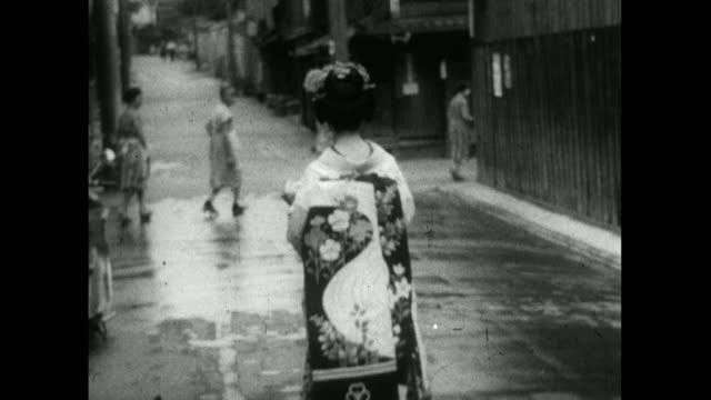geisha walks on street in higashiyama district of kyoto; 1959 - femininity stock videos & royalty-free footage