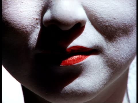 a geisha with traditional red lips and black and red lined eyes on a white face smiles demurely. - ヒトの口点の映像素材/bロール