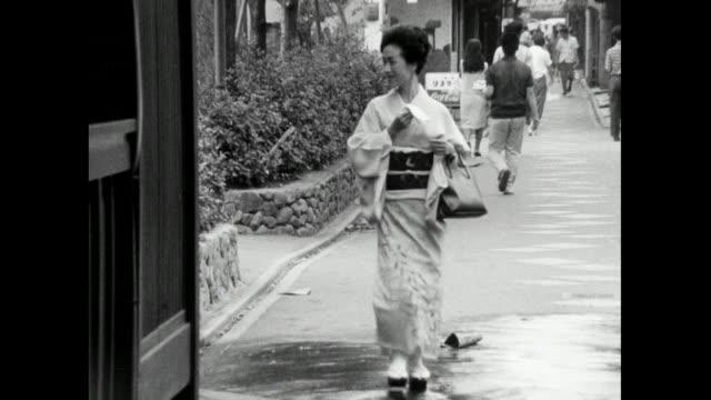 geisha woman walks on paved street in japan; 1966 - femininity stock videos & royalty-free footage