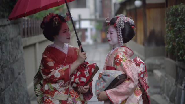 Geishas enjoying a talk while walking outdoors and holding an umbrella
