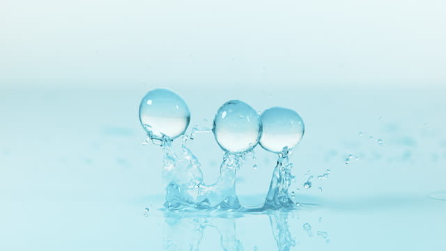 gel balls falling against blue background, slow motion 4k - tre oggetti video stock e b–roll