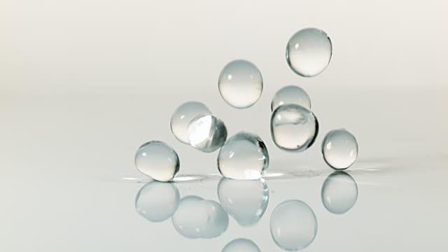 Gel Balls Falling against White Background, Slow Motion 4K