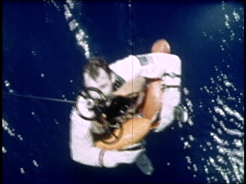 gemini iv astronauts float in inflatable raft before being lifted into helicopter after successful splashdown / atlantic ocean - splashdown stock videos and b-roll footage
