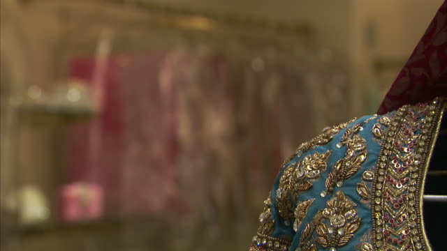 stockvideo's en b-roll-footage met gems cover a garment in a fabric shop in india. - kleding
