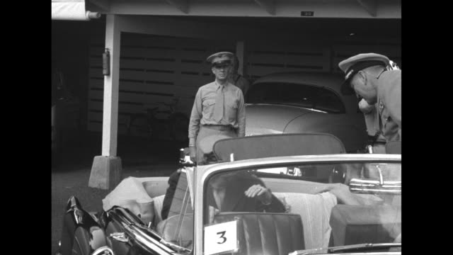 Gen Douglas MacArthur carrying a lei enters a convertible sedan and chats with officer / the cars drive away on road lined with civilians / he and...