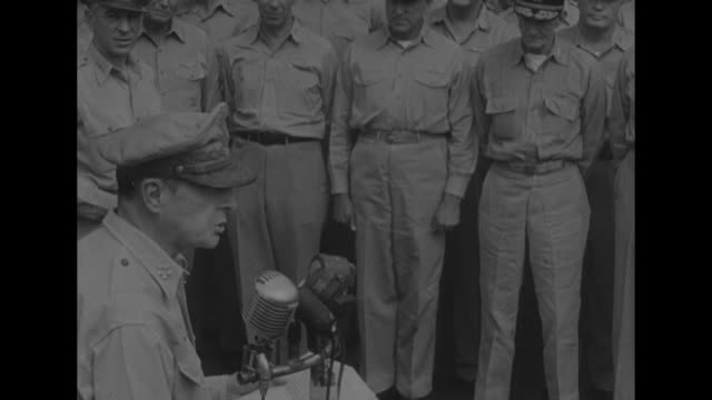 Gen Douglas MacArthur / overhead view of MacArthur standing on deck behind table where surrender was signed Japanese delegation facing him Allied...