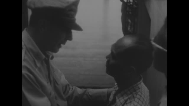 Gen Douglas MacArthur puts hands on shoulders of Filipino man and they talk as MacArthur leaves Malacanang Palace having just turned over the...