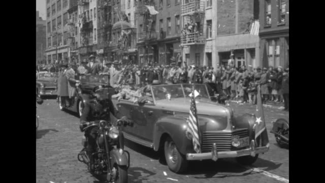 Gen Douglas MacArthur riding in back seat of open car waving at crowd / shot from moving vehicle of crowd on sidewalk confetti flying through air /...