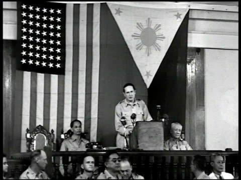 Gen Douglas MacArthur speaking at podium Philippine President Manuel Roxas FG 'Gentlemen of the Congress of the Phil during the battle for Manila I...
