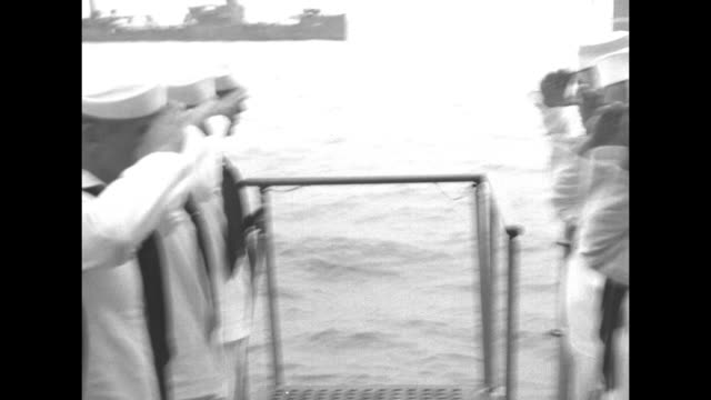 US Gen Douglas MacArthur steps off motor launch onto platform of bottom of steps to ship / two rows of sailors standing at attention at top of steps...