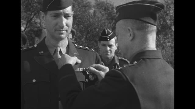 MS Gen Dwight Eisenhower pins Distinguished Service Medal on the jacket of Gen Mark Clark at outdoor ceremony as other officers look on the two...