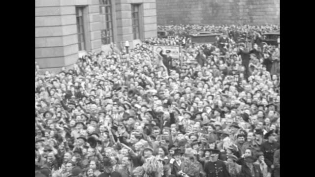Gen Dwight Eisenhower rides in horsedrawn carriage with Sir Arthur Tedder Marshal of the Royal Air Force through huge crowds of cheering Londoners as...