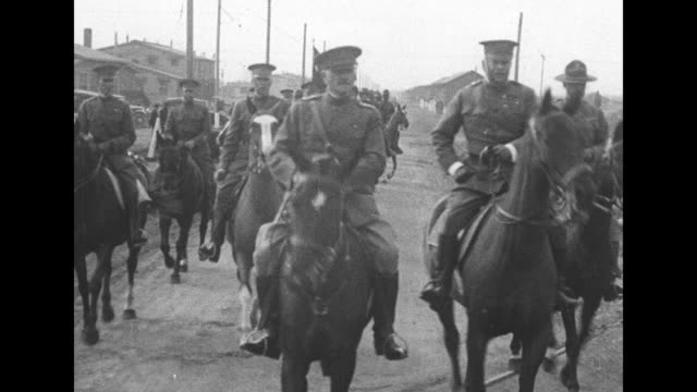 Gen John J Pershing and other officers ride horseback and he salutes soldiers / he walks past artillery caisson / inspecting motorcycles with wooden...