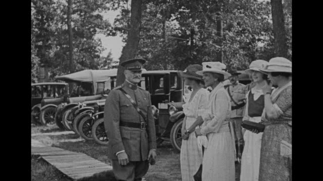 Gen John J Pershing heartily laughing with four women / he stands at attention with several soldiers behind him and chats with civilians then...