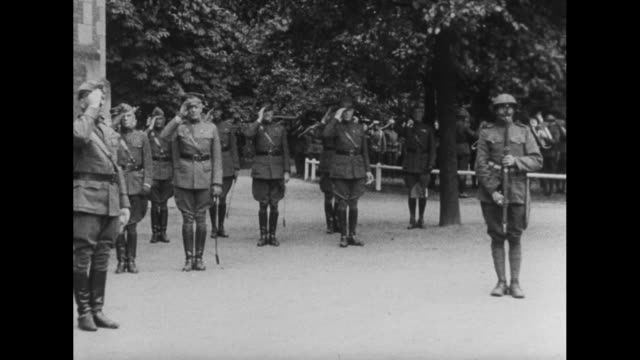 Gen John Pershing Commander of American Expeditionary Force walking with other officers along front of formation of soldiers inspecting them /...