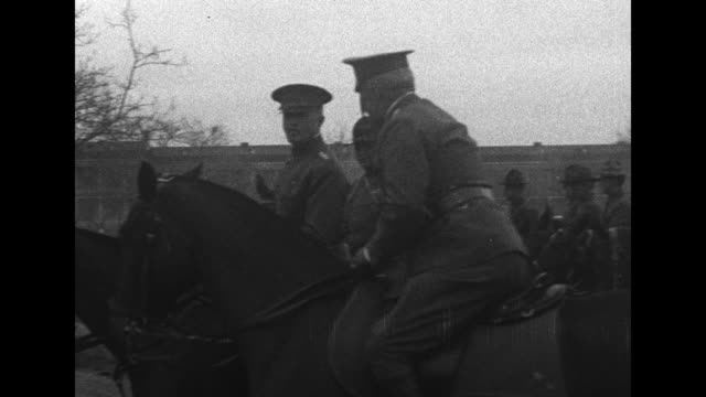 Gen John Pershing watches truck convoy from horseback with numerous other cavalry men / Note exact year not known documentation incomplete