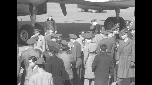 gen. maxwell d. taylor comes down steps of airplane at airport with another officer and is greeted at bottom of steps by general james van fleet,... - vangen stock-videos und b-roll-filmmaterial