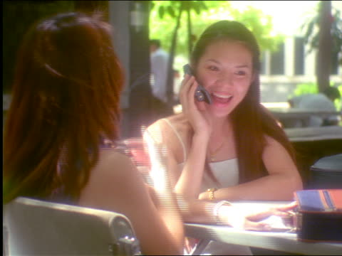 vidéos et rushes de 2 gen x asian women at table talking + sharing cell phone outdoors / 1 waves towards cam / thailand - 1990 1999