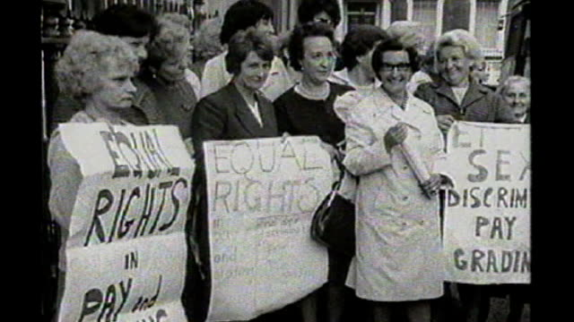 gender pay gap widens / tx group of dagenham women factory workers demonstrating outside the ministry of labour holding placards for equal pay close... - uguaglianza video stock e b–roll