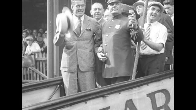 gene tunney, accompanied by a policeman and crowd of men, waves hat from ship's gangplank as he takes a trip prior to his marriage to mary lauder /... - pesi massimi video stock e b–roll