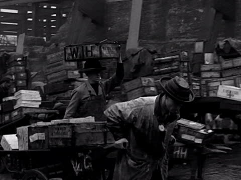 general activity at billingsgate market a porter pulls a cart of crates while another porter carries a crate on his head 1950's - porter stock videos & royalty-free footage