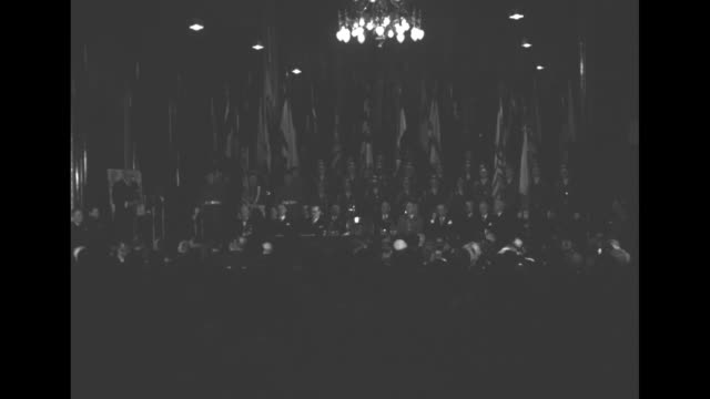 general anthony mcauliffe standing during ceremony / guests in audience sit and listen / wv of large room and head table with many flags mounted... - vangen bildbanksvideor och videomaterial från bakom kulisserna