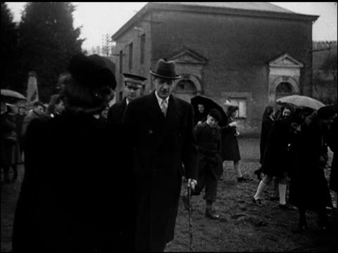 General Charles de Gaulle walking w/ escort stopping to shake hands w/ male roadside walking down road lighting cigarette