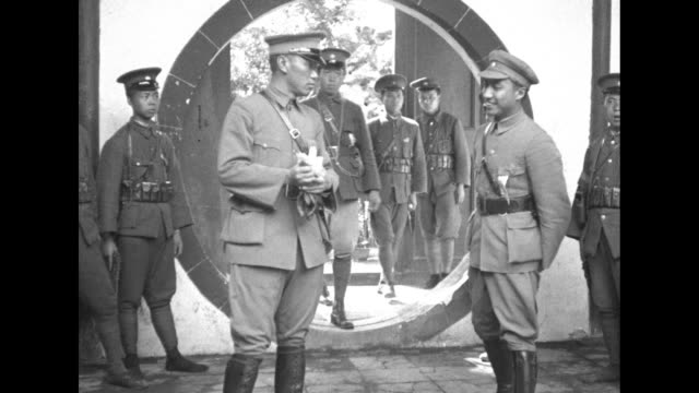 vs general chiang kaishek walks through round portal on grounds at his home toward camera with other military officers standing nearby / chiang... - chiang kai shek stock videos and b-roll footage