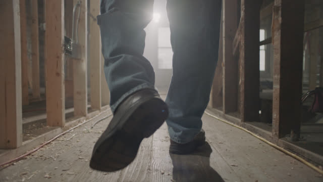 slo mo. general contractor walks on old wooden floorboards in abandoned building. - baugewerbe stock-videos und b-roll-filmmaterial