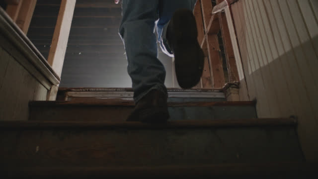 stockvideo's en b-roll-footage met cu slo mo. general contractor walks up stairs in abandoned urban building. - ploegbaas