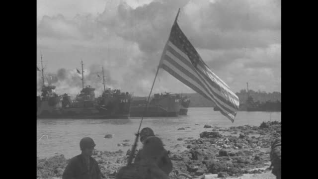 us general douglas macarthur accompanied by officers walking along beach / landing barges grounded near beach soldiers on beach us flag on pole stuck... - general macarthur stock videos & royalty-free footage
