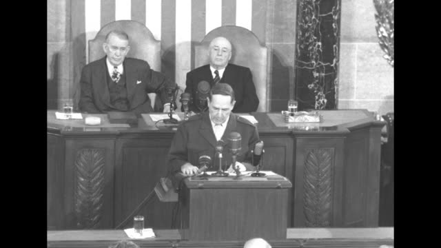 VS General Douglas MacArthur at lectern speaks to joint session of the US Congress Vice President Alben Barkley and Speaker of the House Sam Rayburn...