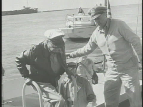 General Douglas MacArthur climbing up onto dock greeting General of the United States Marine Corps Oliver Prince Smith shaking hands Korea 38th...