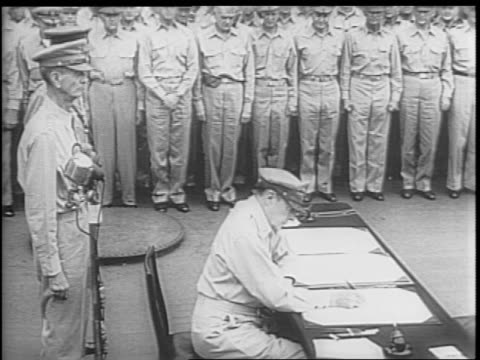 general douglas macarthur invites his fellow officers to accompany him while he signs the document adds his signature and passes the pen off to... - arrendersi video stock e b–roll