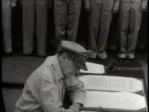 us general douglas macarthur signs the japanese surrender then gives the pen to british general ae percival aboard the uss missouri - japanese surrender stock videos and b-roll footage
