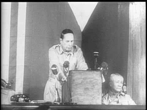 General Douglas MacArthur speaks in front of a special session of the Philippine Congress crowd watching standing ovation MacArthur leaving
