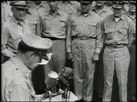 general douglas macarthur standing at microphone on uss missouri speaking ' peace is now restored to the world' hands closing japan instrument of... - arrendersi video stock e b–roll